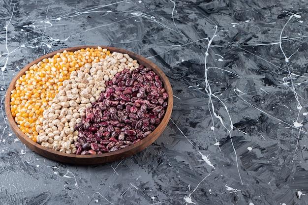 Placa de madeira cheia de grãos crus, ervilhas e feijão em fundo de mármore.