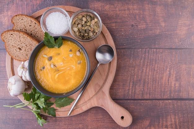Placa de madeira cheia de tigela de sopa e ingredientes