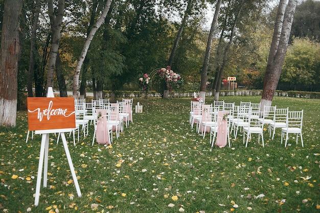 Placa de madeira com a inscrição de boas-vindas. cerimônia de casamento pronta com cadeiras e uma decoração