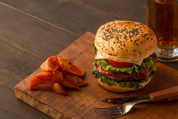 Placa de madeira com batatas fritas e hambúrguer