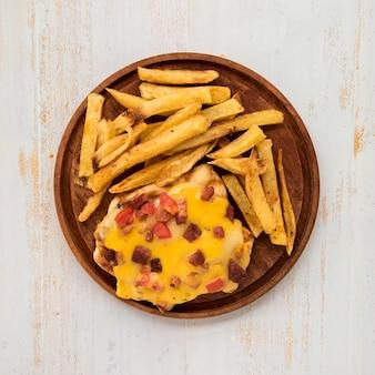 Placa de madeira com batatas fritas e omelete na mesa pintada