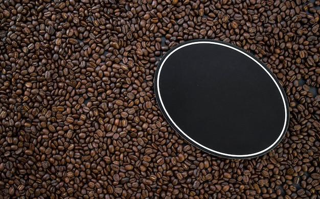 Placa de madeira com café quente e feijão no fundo da mesa de madeira