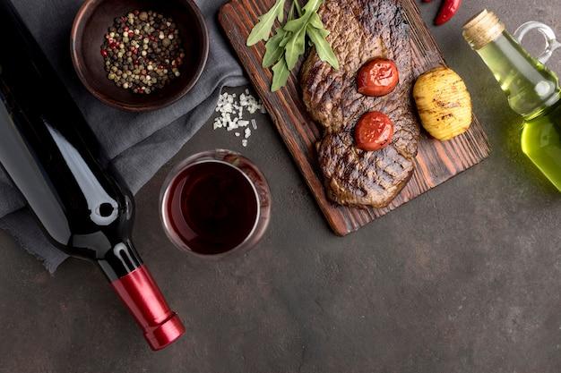 Placa de madeira com carne grelhada e vinho