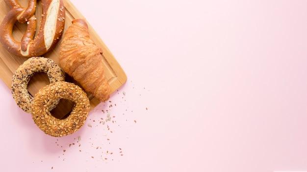 Placa de madeira com espaço para texto e pretzel e croissant
