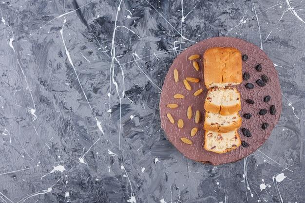 Placa de madeira com fatias de bolos de passas na superfície de mármore.