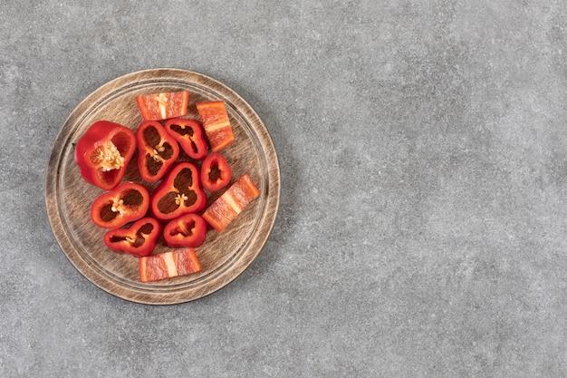 Placa de madeira com fatias de pimentão vermelho fresco na superfície de mármore.