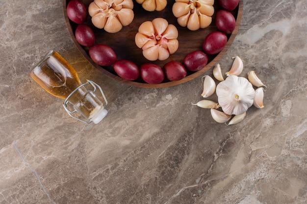 Placa de madeira com frutas fermentadas e alho na mesa de pedra.