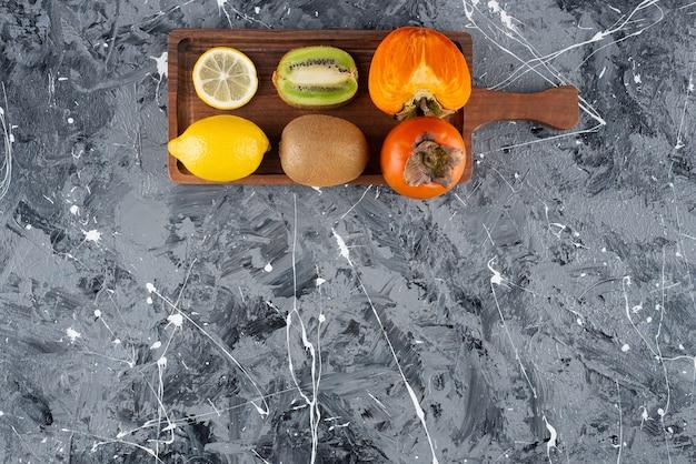 Placa de madeira com frutas frescas inteiras e fatiadas no fundo.