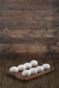 Placa de madeira com ovos brancos crus na mesa de madeira.