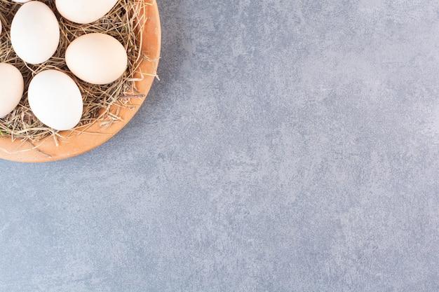 Placa de madeira com ovos brancos crus na mesa de pedra.