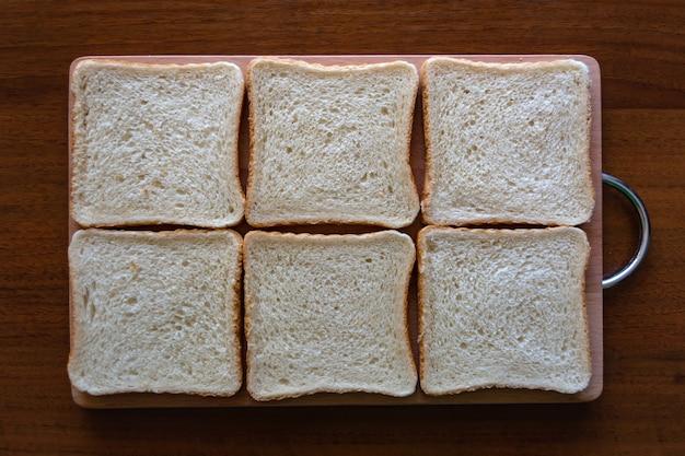 Placa de madeira com pão torrado saboroso na tabela.
