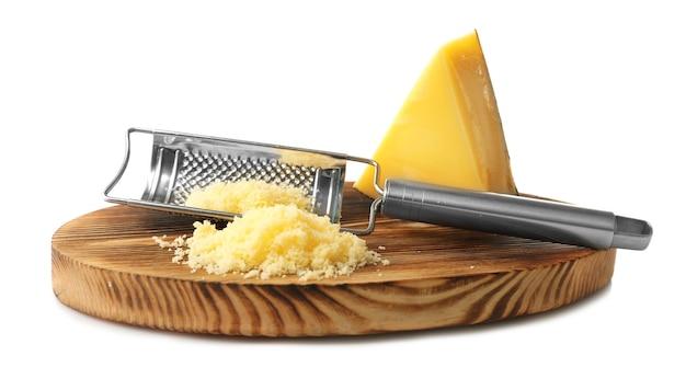 Placa de madeira com ralador de metal e queijo isolado no branco