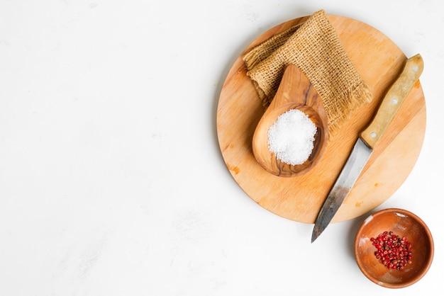 Placa de madeira com sal natural e papel vermelho em uma tigela pequena para cozinhar alimentos frescos e deliciosos