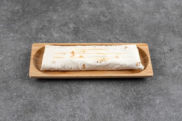 Placa de madeira com sanduíche de frango grelhado na mesa de mármore.