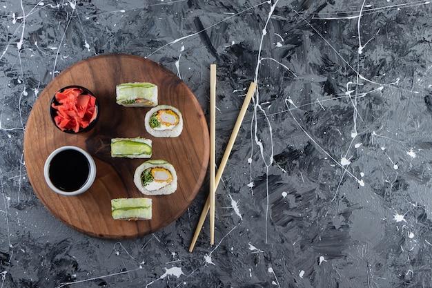 Placa de madeira com sushi de dragão verde rola em fundo de mármore.