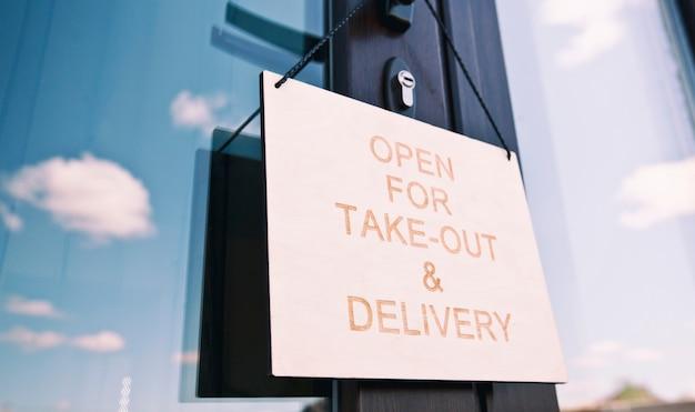 Placa de madeira com texto: aberto para take-out e entrega pendurado na porta no café