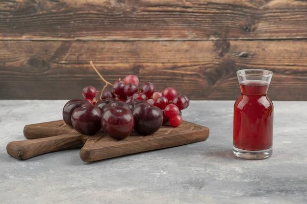 Placa de madeira de ameixas vermelhas frescas e uvas com copo de suco na superfície de mármore.