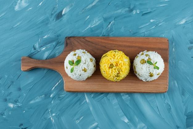 Placa de madeira de arroz cozido com ervilhas verdes na superfície azul.