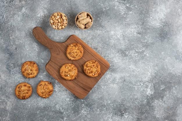 Placa de madeira de biscoitos caseiros com amendoim orgânico na mesa de mármore.