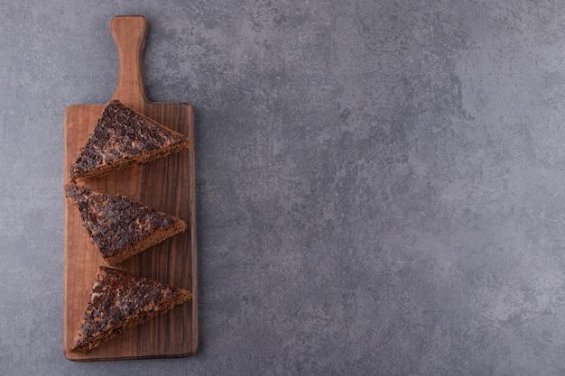Placa de madeira de bolo doce fatiado na mesa de pedra.