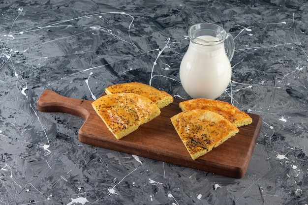 Placa de madeira de bolos frescos fatiados e copo de leite no fundo de mármore.