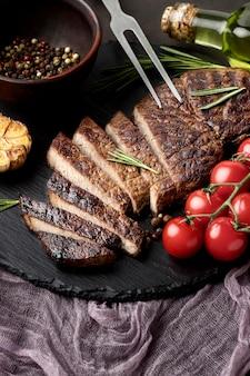 Placa de madeira de close-up com saborosa carne cozida