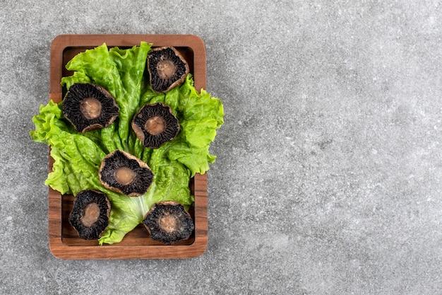Placa de madeira de cogumelos fritos com alface na mesa de pedra.