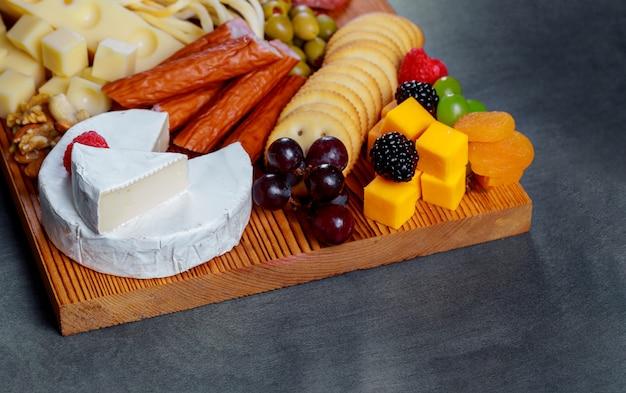 Placa de madeira de corte com queijo sortido fresco e bolachas de carne