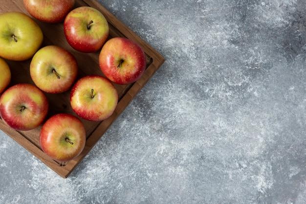 Placa de madeira de deliciosas maçãs frescas na superfície de mármore.