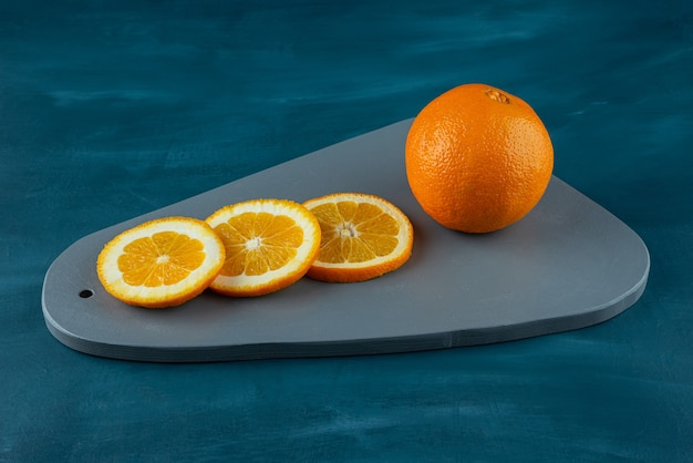 Placa de madeira de fatias de laranjas suculentas na superfície azul.