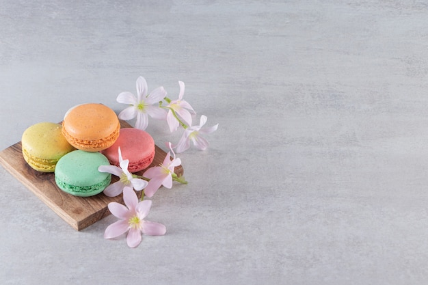 Placa de madeira de macaroons doces coloridos com flores na superfície de pedra
