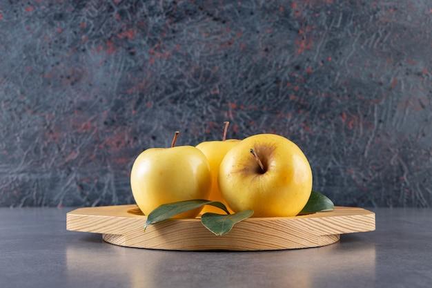 Placa de madeira de maçãs amarelas com folhas verdes na pedra.