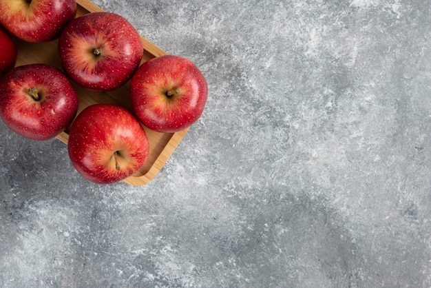 Placa de madeira de maçãs vermelhas brilhantes na mesa de mármore.