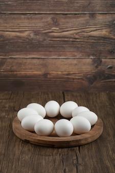 Placa de madeira de ovos orgânicos crus na superfície de madeira.