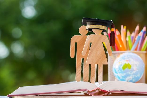 Placa de madeira de pessoas com chapéu de formatura no livro aberto