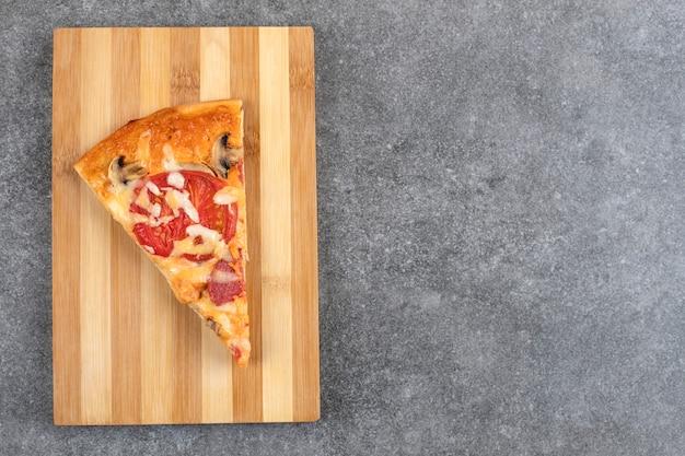 Placa de madeira de saborosa pizza caseira na mesa de pedra.