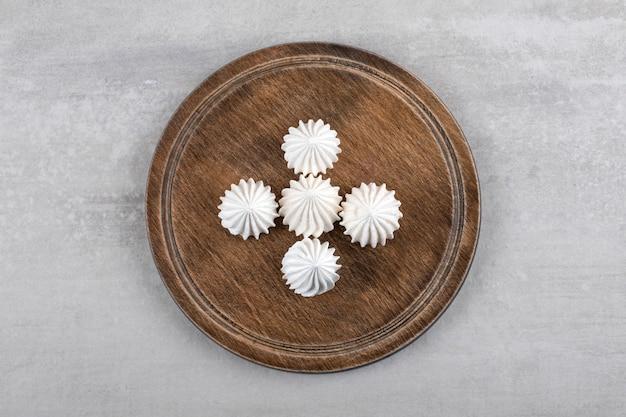 Placa de madeira de sobremesa de merengue branco na mesa de pedra.