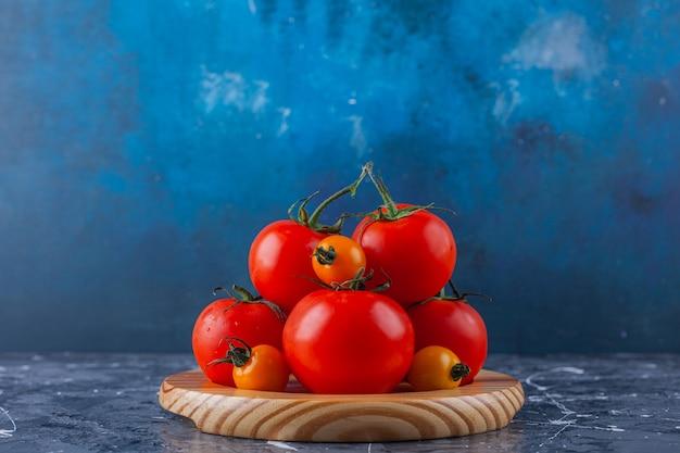 Placa de madeira de tomate cereja e vermelho na superfície de mármore.