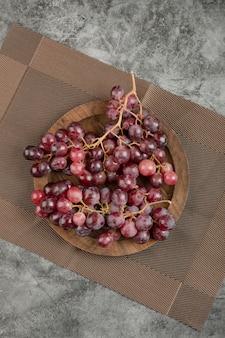 Placa de madeira de uvas vermelhas colocada sobre superfície de mármore.