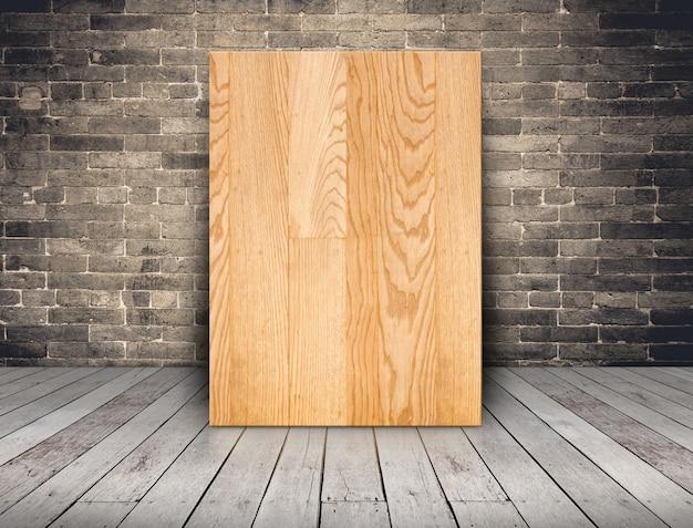 Placa de madeira em branco prancha na parede de tijolo de grunge e piso de tábua de madeira