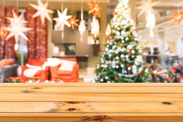 Placa de madeira em cima da mesa vazia de fundo desfocado. perspectiva mesa de madeira marrom sobre borrão de árvore de natal e fundo de lareira, pode ser usado mapeado para apresentação de produtos de montagem ou layout de design