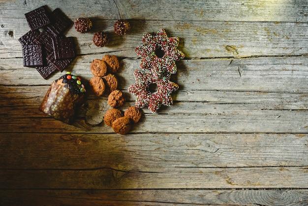 Placa de madeira envelhecida retrô com biscoitos de chocolate e doces em um canto com espaço para texto