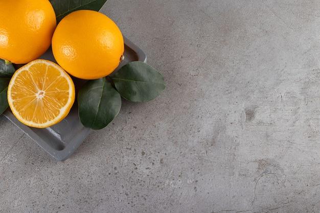 Placa de madeira escura de laranjas frescas suculentas na mesa de pedra.