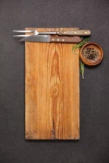 Placa de madeira, faca e garfo