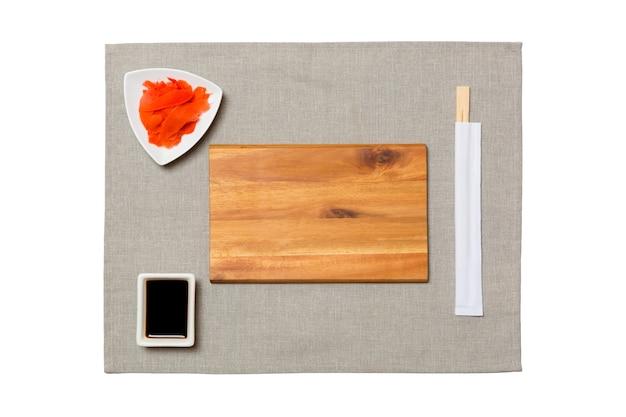 Placa de madeira marrom retangular vazia com pauzinhos para sushi, gengibre e molho de soja em fundo de guardanapo cinza. vista superior com espaço de cópia para você projetar.