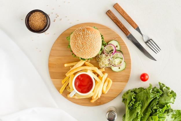 Placa de madeira plana leiga com hambúrguer e batatas fritas