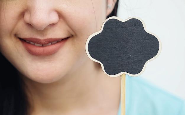 Placa de madeira preta closeup em forma de caixa de texto com rosto sorriso borrado de fundo de mulher