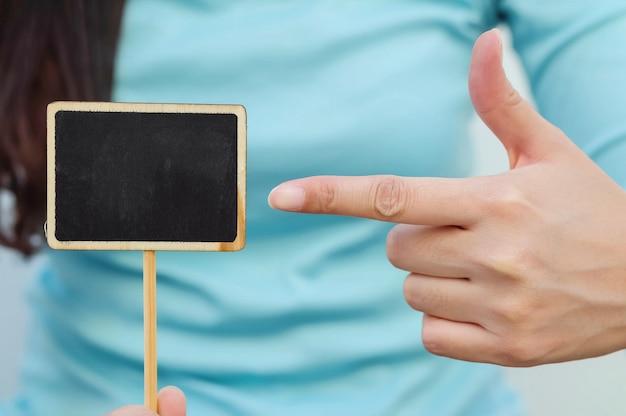 Placa de madeira preta closeup em forma quadrada com o dedo da mulher aponte para o conselho