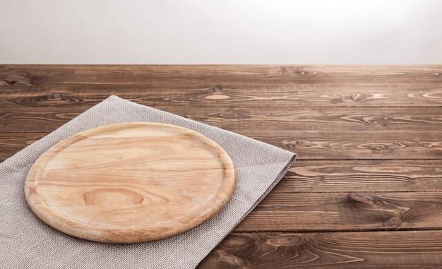 Placa de madeira redonda com toalha de mesa.
