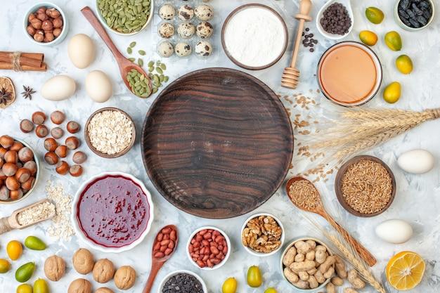 Placa de madeira redonda de vista superior com ovos de geleia, nozes e sementes diferentes em uma massa branca, bolo de açúcar, biscoito de cor doce, foto de nozes